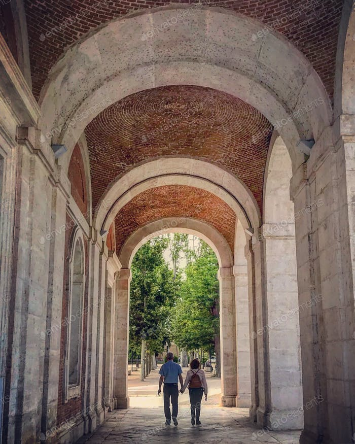Couple walking holding hands in arches with diminishing perspective.