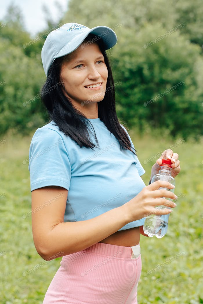 Young smiling woman drinking water bottle in green background at run training exercise yoga workout