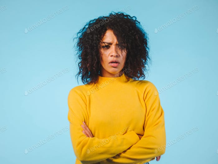 Angry annoyed young housewife keeping arms crossed and staring at camera with sceptical and
