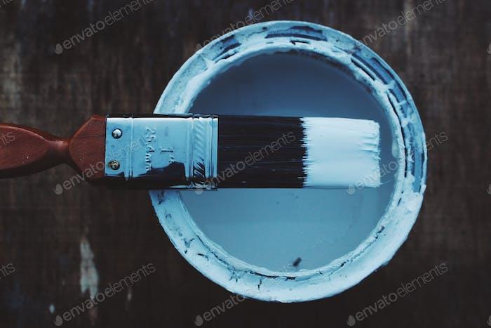 A paint brush sat on a pot of paint
