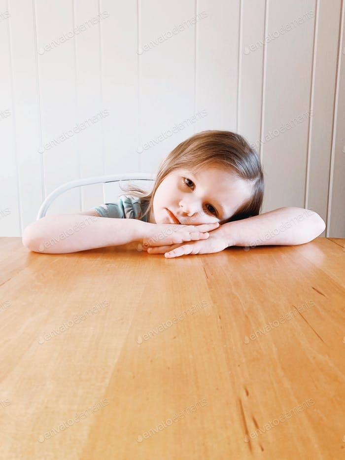 Bored little girl sitting at a table, laying her head on her arms.