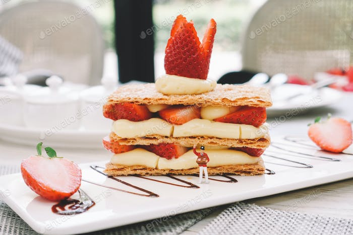 Mille-feuille, layered dessert with cream and strawberry. mini figure