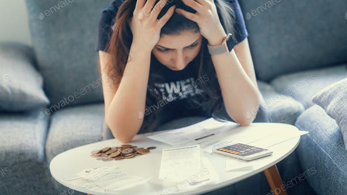A broke woman making the end of the month calculations, and has no money left to pay for the bills.