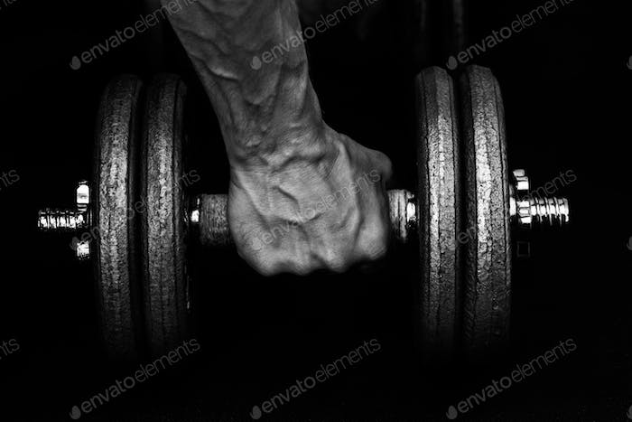Fist gripping a 20kg dumbbell at the gym.