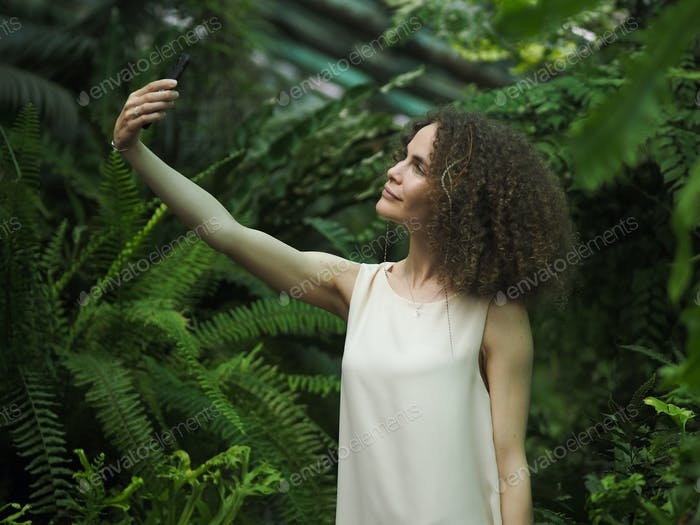 Young beautiful woman with curly hair makes selfie on the background of trees in a botanical garden.