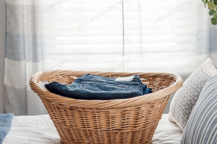 Basket of neatly folded clothes on the bed