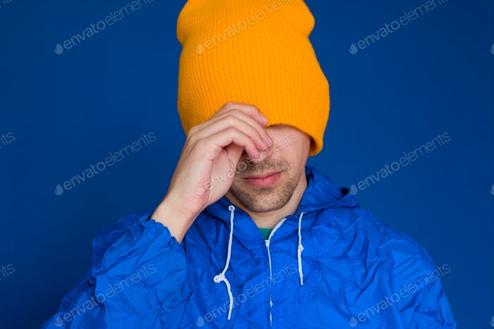 young man in a blue sport 90s style jacket and yellow hat portrait ,man hiding his face under  cap