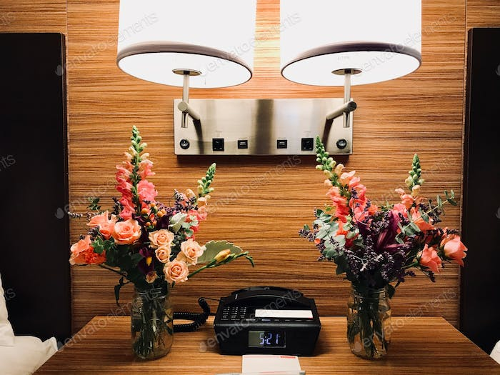 Nightstand in a hotel room with flowers, telephone, clock and lamps