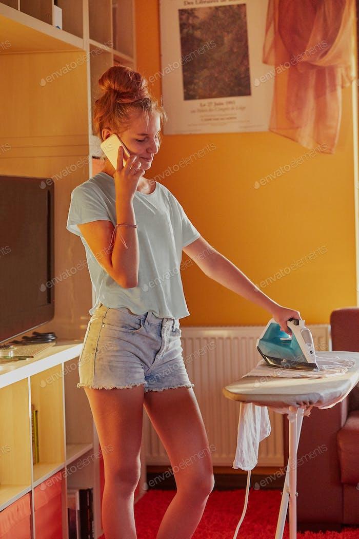 Junge Frau bügelt ihre Kleidung und spricht gleichzeitig auf einem Smartphone