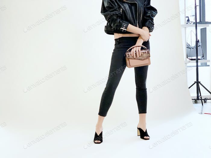 Model (not showing her face) during a photoshoot holding a purse again a white background.