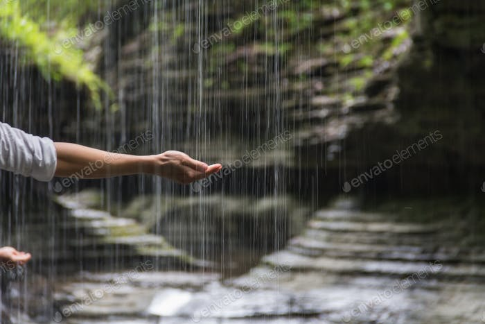 Opening one's hand to touch and feel the cooling water of the waterfall that mother nature offer