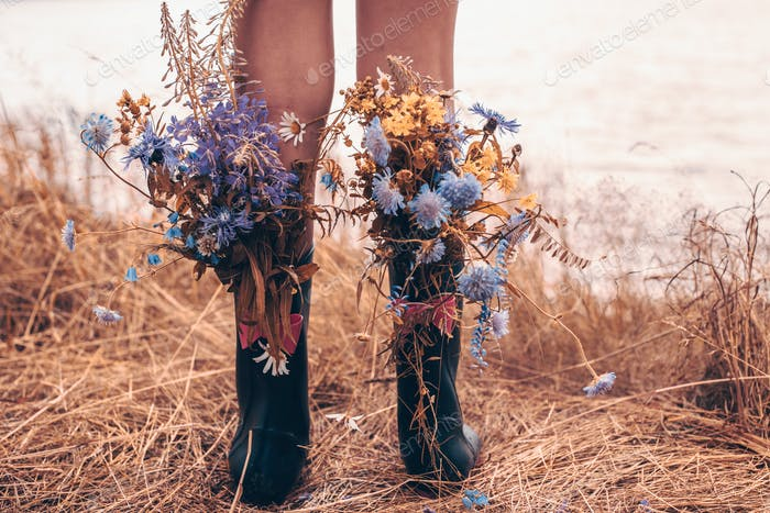 girl in rain boots with wild flowers