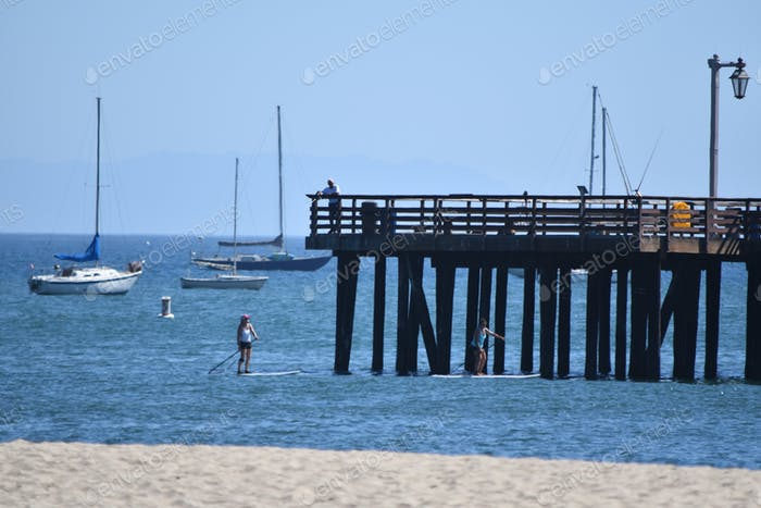 Paddleboarder beneath the dock in Santa Barbara with sailboats anchored offshore