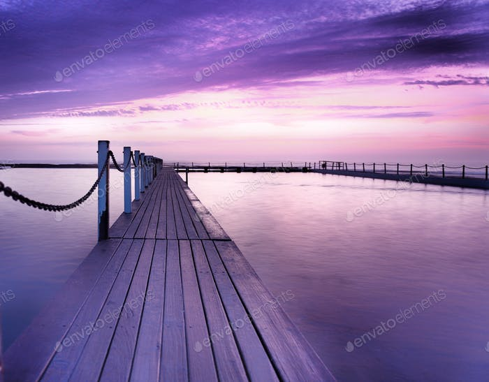 A purple sunrise across one of Sydney's ocean pools