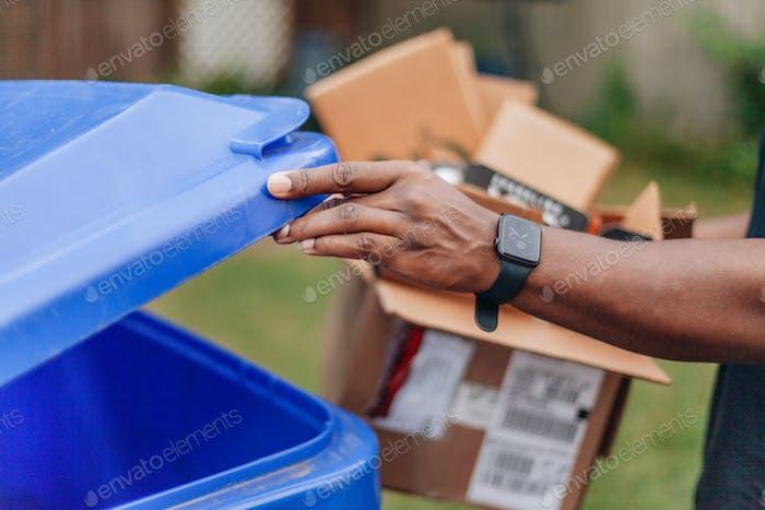 Afroamerikaner zu Hause steckt Pappschachtel in blauen Recyclingbehälter, umweltfreundlich