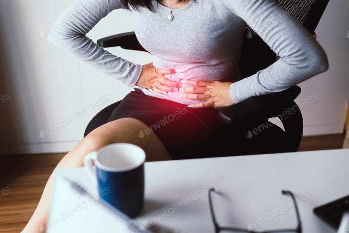 Woman having painful stomach ache during working from home