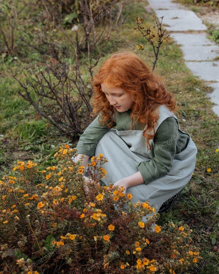 Rothaarige kleine Mädchen in einem Leinenkleid schneidet einen blühenden Busch ab.