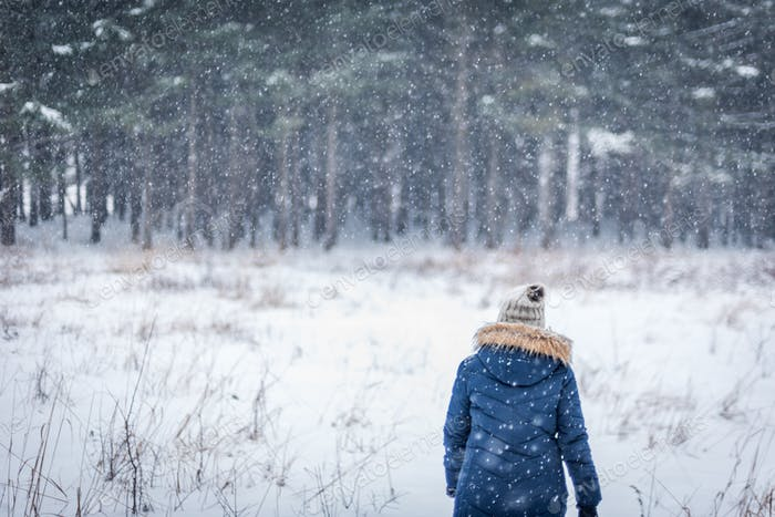 woman walking into winter woods with snow falling active