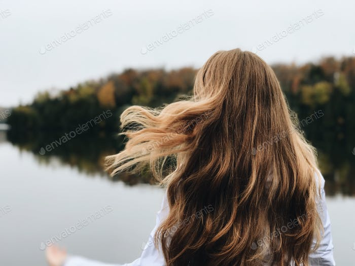 Woman outdoors by reflecting Lake