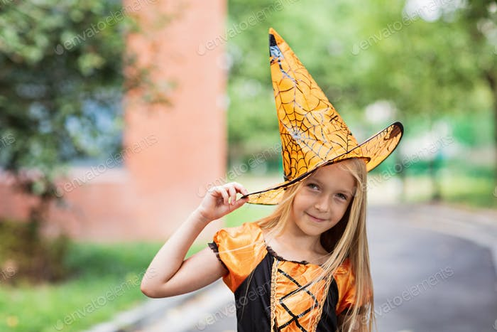 Candid portrait of Little blonde Girl in costume of witch in park. Happy Halloween concept