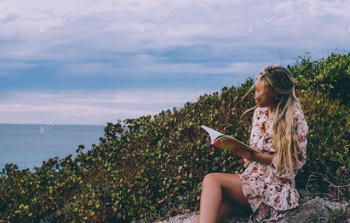 Frau mit langen Haaren liest ein Buch im Freien