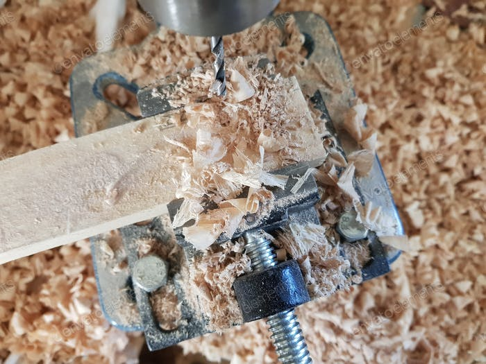 Close-up of drill press, drill bit, drilling through a piece of wood.