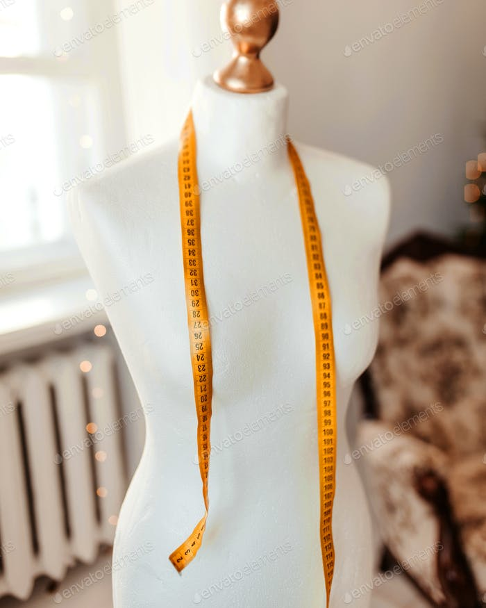 orangefarbenes Maßband auf weißem Manikin