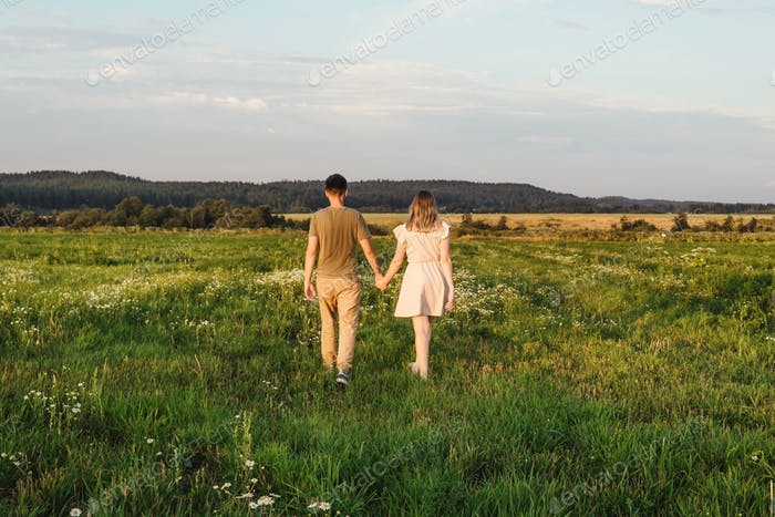 Walking loving couple in the field. Sunset.