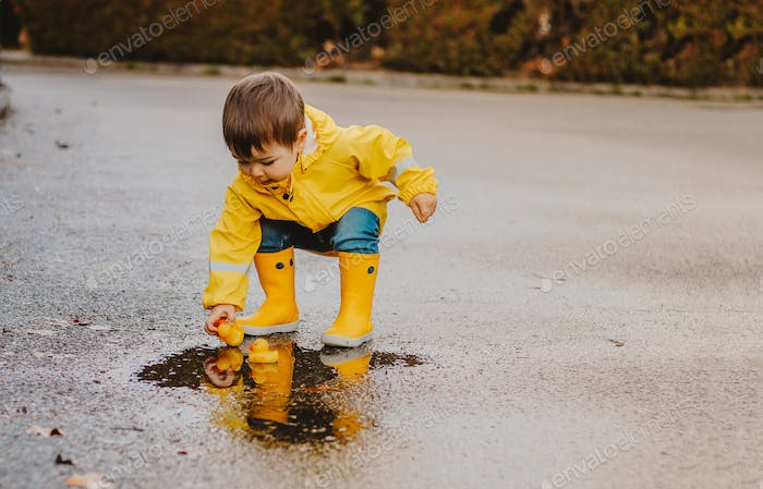 ⭐️Nominated ⭐️Cute playful little baby boy in bright yellow raincoat and rubber boots playing with