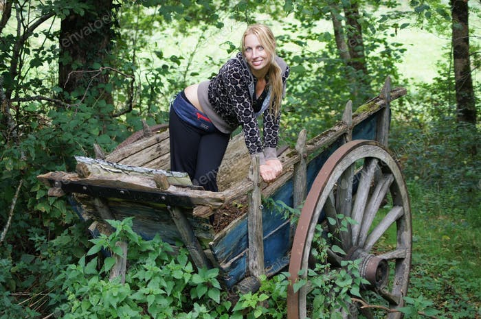 Young blond woman posing on an old carriage in the forest