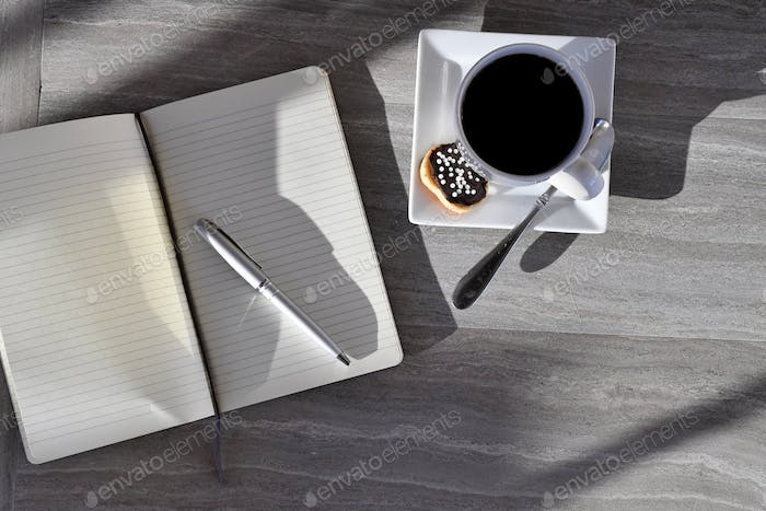 Blank page in journal diary notebook with pen & mug. planning fresh start making lists light shadows