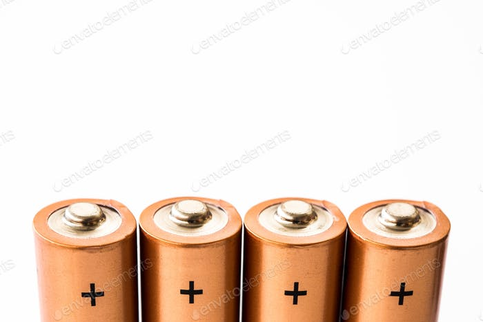 close-up of the positive terminals of disposable alkaline batteries on white background copy space