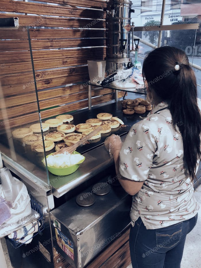 """Young Hispanic Latino woman in her small """"arepas"""" business in a tiny space next to a parking spot."""