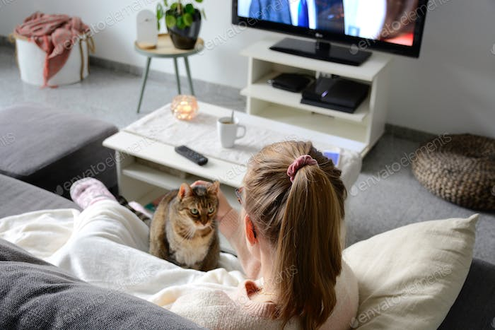 Watching tv. Domestic life with pet. A young woman is sitting on the couch in living room with cat