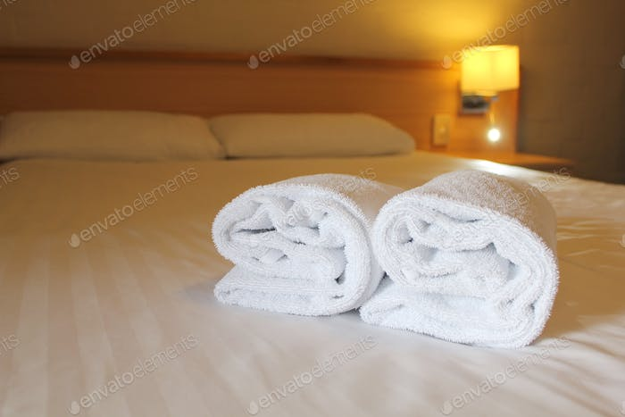 Bedside lamp, pillows and hotel room bed with fresh towels laid out