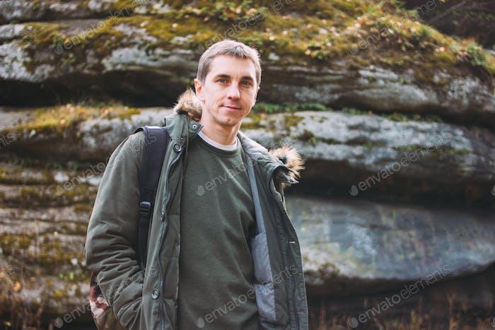 Porträt eines jungen Mannes in khakifarbener Parka-Jacke mit Rucksack, Reise-Abenteuer-Lifestyle