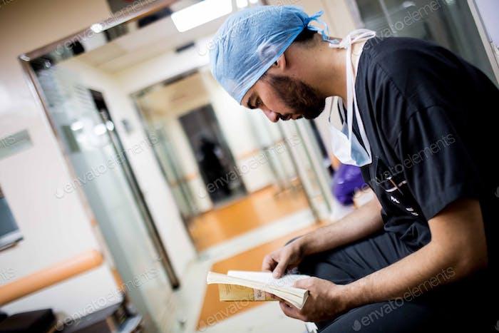 Arzt lesen ein Buch und warten Operation