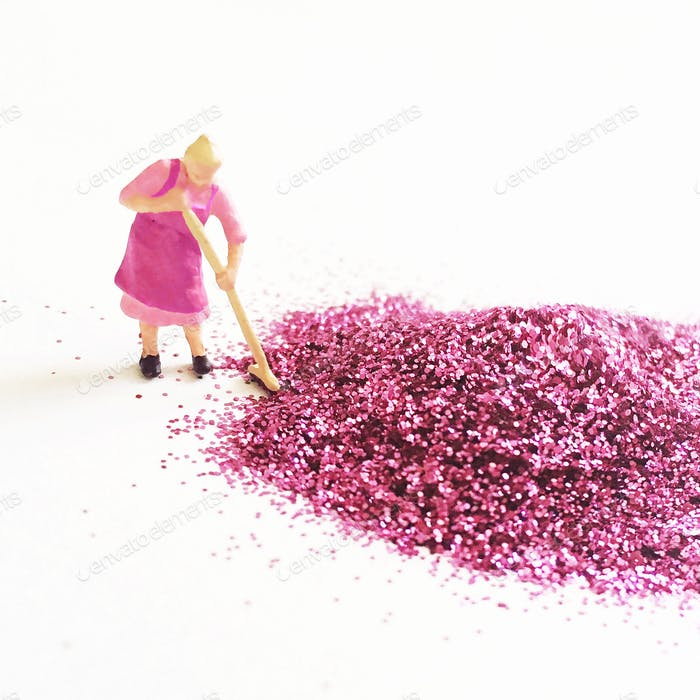 A tiny HO scale woman sweeping up pink glitter on a white background.