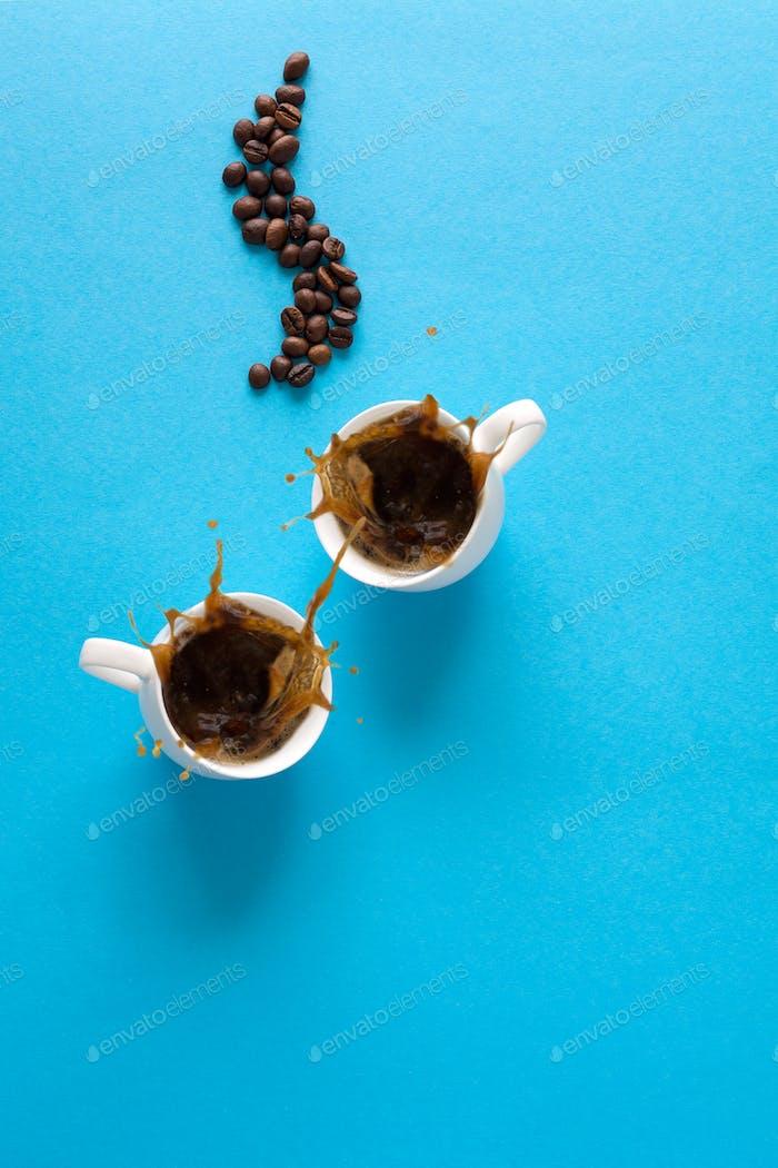 Tassen mit Espresso-Splash, Untertassen, Teelöffel und Kaffeebohnen auf blauem Papierhintergrund