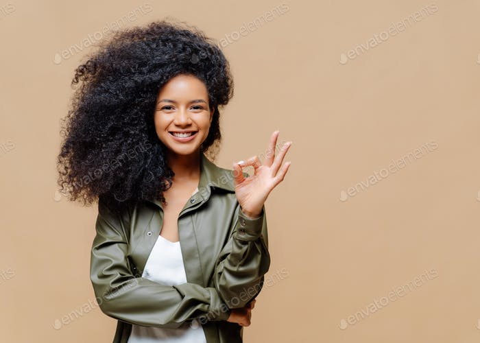 Pleasant looking curly woman has pleasant smile, makes okay gesture, excellent sign, gives approval