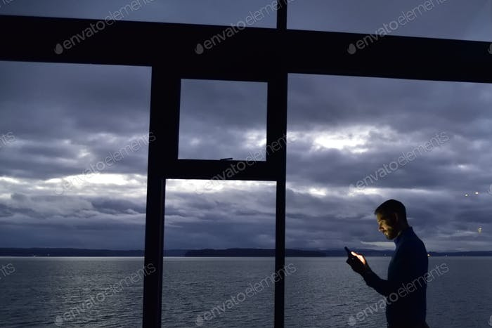 Using tech by windows at dusk