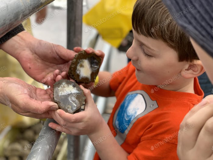 Little boy seen the inside of the geode at a rock and gem show