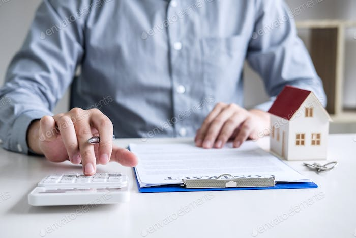 Businessman working doing finances and calculation cost of real estate investment while be signing