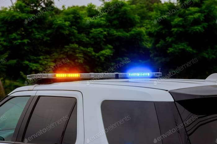 Blue and red flashing sirens of police car during the cruiser flashing red and blue emergency lights