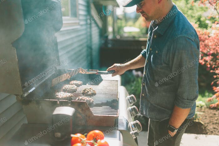 A man barbecuing burgers in the backyard.