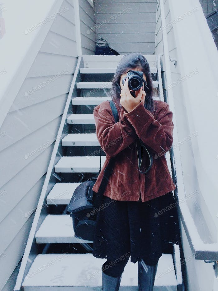 Girl in a chic jacket taking a picture with camera in snow storm weather