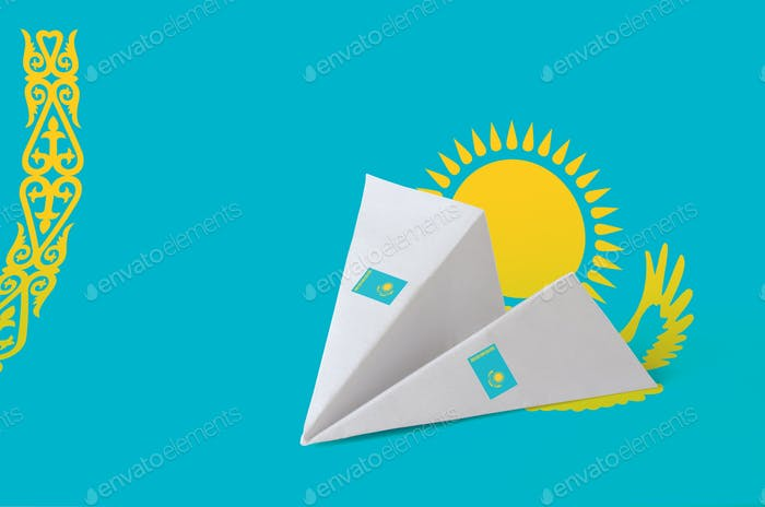 Kazakhstan flag depicted on paper origami airplane. Oriental handmade arts concept