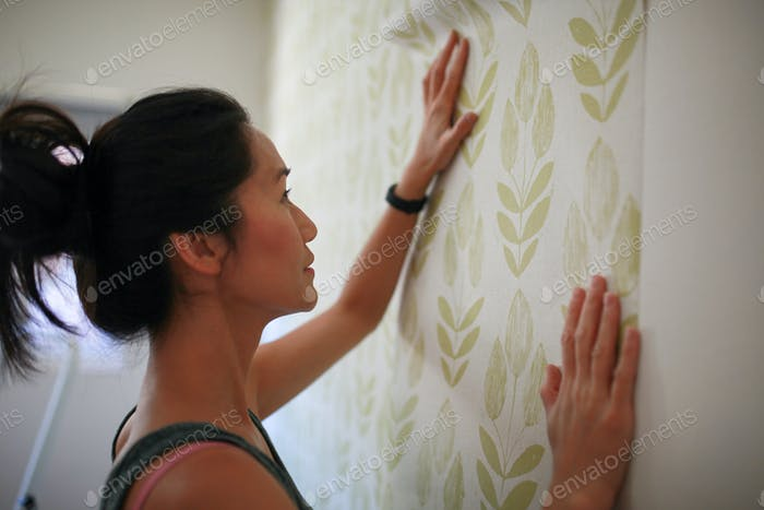 Woman doing a home improvement project: hanging wallpaper