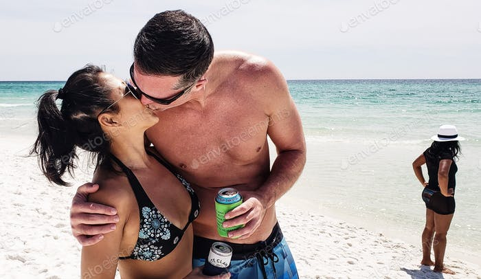 Two millennials at the beach kissing each other and drinking beer while on vacation and showing thei