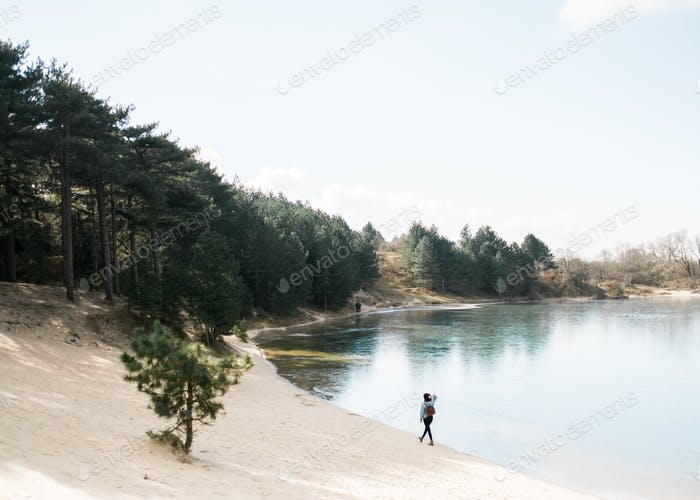Young woman walking next to a lake, traveling solo. Hiking through the forest